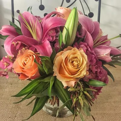 pink-orientals-with-hydrangea-and-orange-colombian-roses-with-lush-foliage